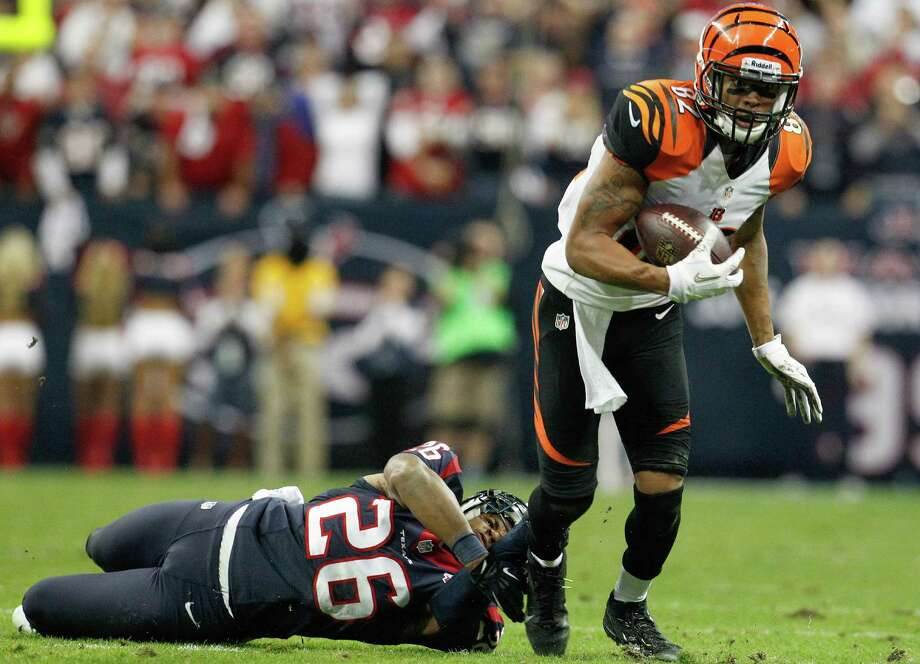 Texans defensive back Brandon Harris (26) hangs on to Bengals wide receiver Marvin Jones (82) on a fourth down stop during the fourth quarter. Photo: Karen Warren, Houston Chronicle / © 2012 Houston Chronicle