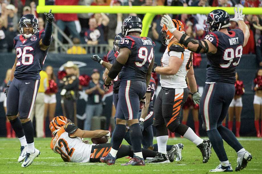 Texans defensive back Brandon Harris (26), defensive end Antonio Smith (94) and defensive end J.J. Watt (99) celebrate after stopping Bengals wide receiver Marvin Jones (82) on a fourth down play during the fourth quarter. Photo: Smiley N. Pool, Houston Chronicle / © 2013  Houston Chronicle
