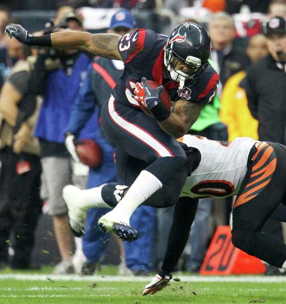 Texans running back Arian Foster (23) leaps up as he tries to avoid the tackle of Bengals free safet