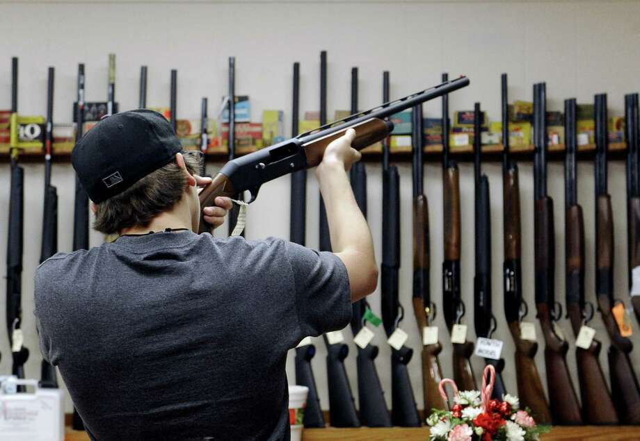 A customer handles a shotgun at a shop in College Station. Readers blame the lack of concealed weapons, the Second Amendment and Hollywood for mass killings. Photo: Pat Sullivan, Associated Press / AP