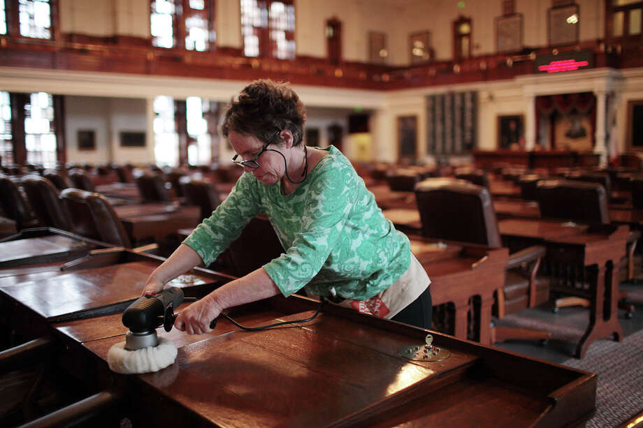 Contract worker Mara Eurich reconditions desks in the Texas House of Representatives last week. The Legislature will begin a new session Tuesday. Photo: Jerry Lara, San Antonio Express-News / © 2012 San Antonio Express-News