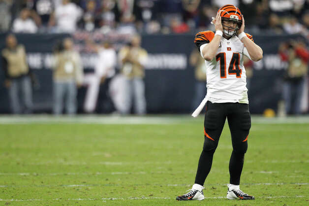 Cincinnati Bengals quarterback Andy Dalton holds his helmet trying to listed to a play call during the fourth quarter of an AFC playoff game against the Houston Texans at Reliant Stadium on Saturday, Jan. 5, 2013, in Houston. Photo: Brett Coomer, Houston Chronicle / © 2013  Houston Chronicle