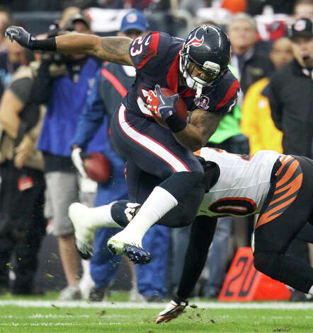 Texans running back Arian Foster (23) leaps up as he tries to avoid the tackle of Bengals free safety Reggie Nelson (20) during the first quarter. Photo: Karen Warren, Houston Chronicle / © 2012 Houston Chronicle