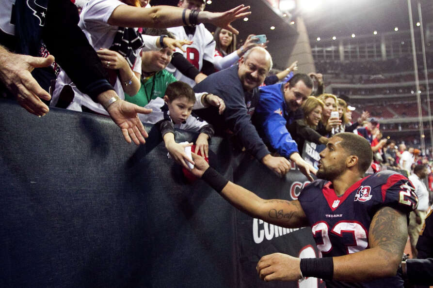 Houston Texans running back Arian Foster (23) hands a souvenir to a young fan after the Texans beat