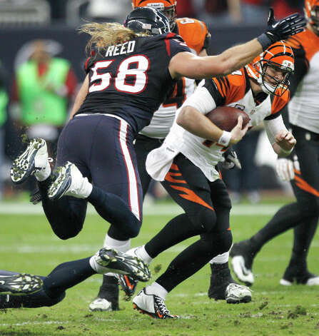 Cincinnati Bengals quarterback Andy Dalton (14) is pressured by Houston Texans outside linebacker Brooks Reed (58) and defensive and J.J. Watt (99) during the fourth quarter of an AFC playoff game at Reliant Stadium on Saturday, Jan. 5, 2013, in Houston. Photo: Brett Coomer, Houston Chronicle / © 2013  Houston Chronicle