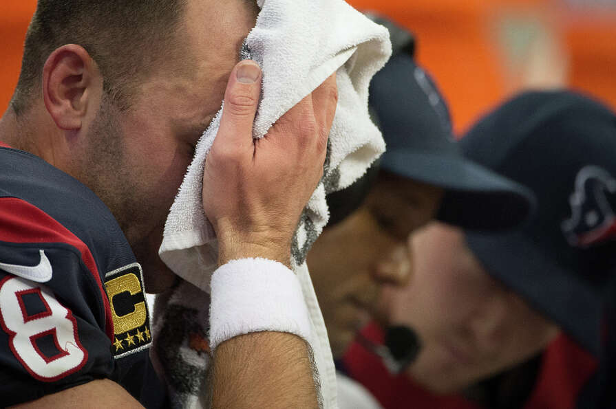 Texans quarterback Matt Schaub wipes his face as he sits on the bench with quarterbacks coach Karl D