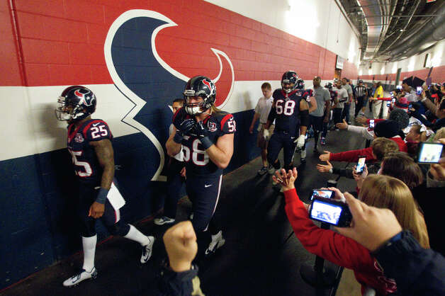 Houston Texans players walk past a line of fans on their way to the field for an AFC playoff game against the Cincinnati Bengals at Reliant Stadium on Saturday, Jan. 5, 2013, in Houston. Photo: Brett Coomer, Houston Chronicle / © 2013  Houston Chronicle