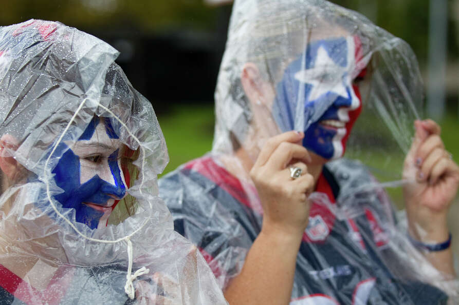 Houston Texans fans Brookelyn Mitchell, left, and Jen Schaefer walk outside Reliant Stadium on their