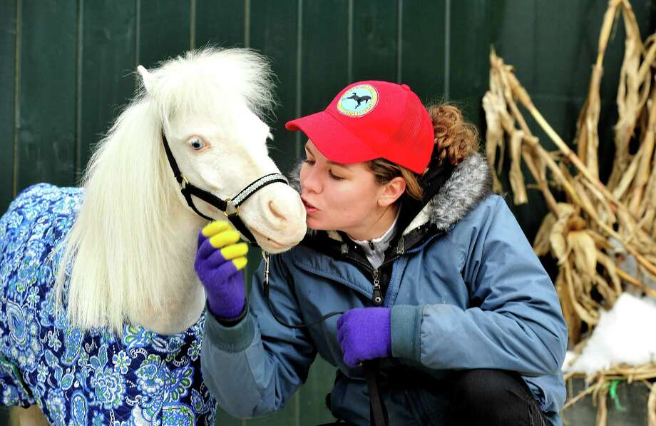 Therapy volunteer Jennifer Anfinsen cuddles with Aladdin, one of the Gentle Carousel Miniature Therapy Horses visiting The Ridge Equestrian Center in Newtown Friday, Jan. 4, 2012. Photo: Michael Duffy / The News-Times
