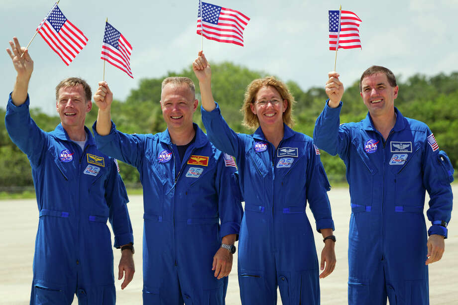 July 4, 2011 | The STS-135, commander Chris Ferguson, pilot Doug Hurley and mission specialists Sandy Magnus and Rex Walheim, wave American flags in honor of the Fourth of July as they arrive at the Kennedy Space Center in preparation for launch. Photo: Smiley N. Pool, Houston Chronicle / © 2011  Houston Chronicle