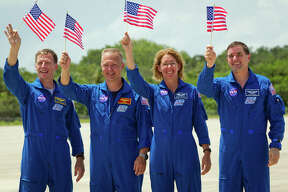 July 4, 2011 | The STS-135, commander Chris Ferguson, pilot Doug Hurley and mission specialists Sandy Magnus and Rex Walheim, wave American flags in honor of the Fourth of July as they arrive at the Kennedy Space Center in preparation for launch.