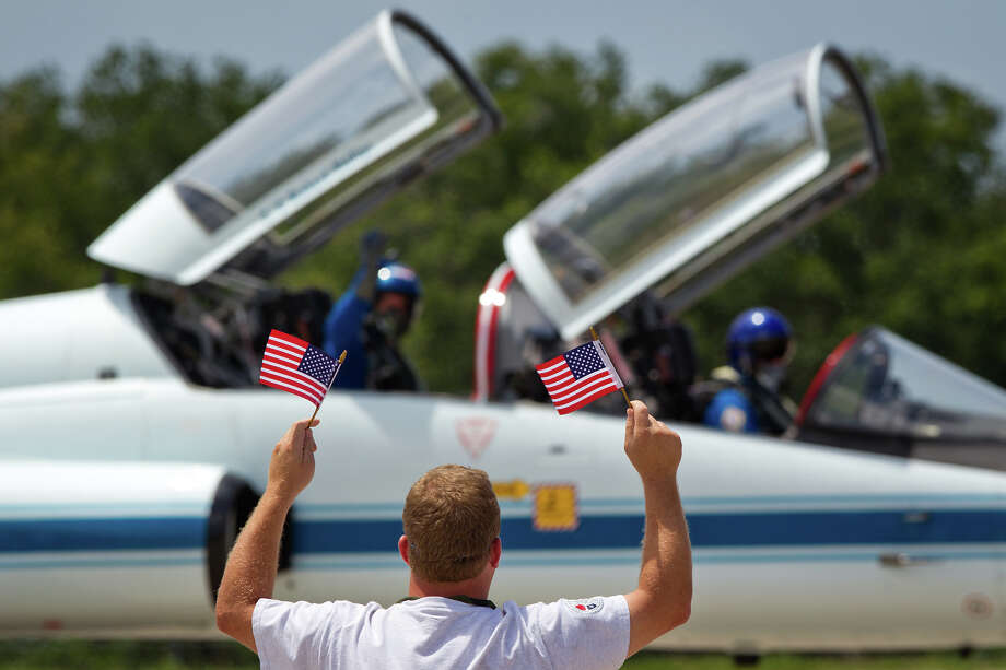 July 4, 2011 | A grounds crew worker holds up American flags in honor of the Fourth of July as Rex Walheim waves back as he and pilot Doug Hurley arrive in a T-38 jet after landing at the Shuttle Landing Facility. Photo: Smiley N. Pool, Houston Chronicle / © 2011  Houston Chronicle