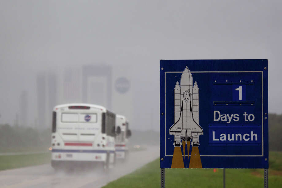 July 7, 2011 | A sign counts down the days to launch as tour buses pass in a heavy downpour at the Kennedy Space Center in Florida. Thunderstorms and an unfavorable forecast for launch day  threatened the scheduled final shuttle launch. Photo: Smiley N. Pool, Houston Chronicle / © 2011  Houston Chronicle