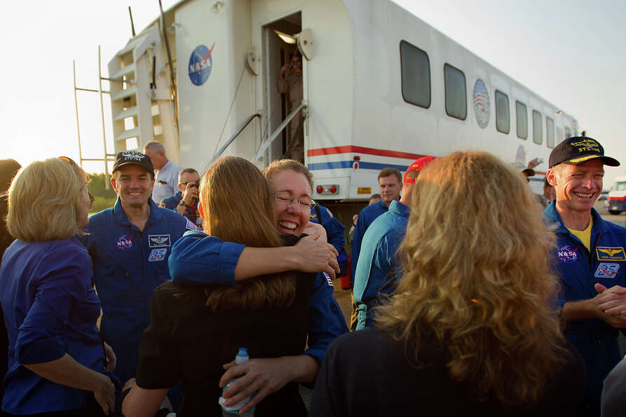 July 21, 2011 | Mission specialist Sandy Magnus gets a hug after emerging from the spacecraft with h