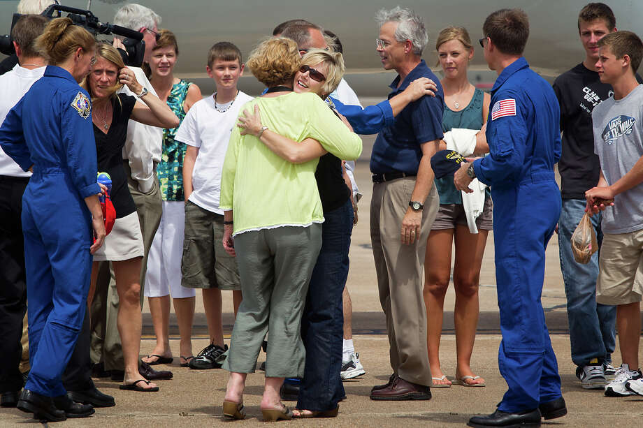 July 22, 2011 | Sandy Ferguson, center, wife of commander Chris Ferguson, right, hugs Rose Magnus, mother of mission specialist Sandy Magnus, left, as the crew  arrives at Ellington Field in Houston. Photo: Smiley N. Pool, Houston Chronicle / © 2011  Houston Chronicle