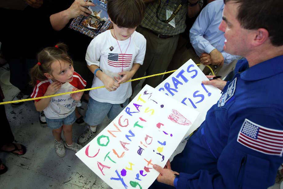 July 22, 2011 | Annabelle Euker gives her handmade signs of congratulations to STS-135 mission specialist Rex Walheim at Ellington Field. Photo: Smiley N. Pool, Houston Chronicle / © 2011  Houston Chronicle