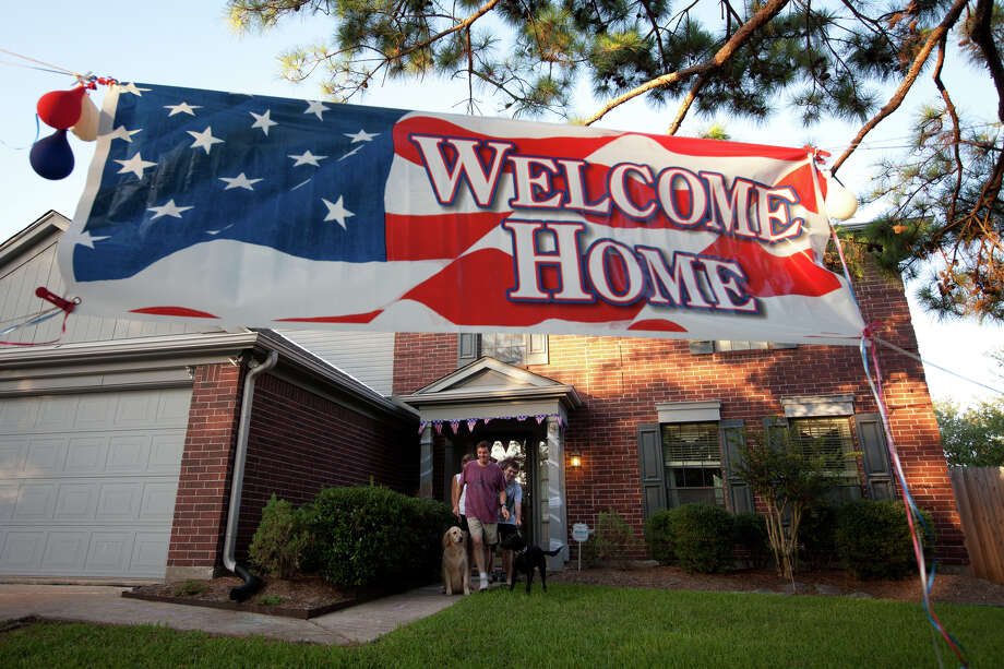 July 23, 2011 | Signs left by neighbors decorate the front yard of their home as Rex Walheim goes for a walk with his family after he returned to his home in Houston. Photo: Smiley N. Pool, Houston Chronicle / © 2011  Houston Chronicle