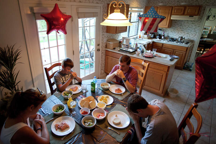 July 23, 2011 | Rex Walheim prays with his family as they sit down to dinner a day after returning from the Kennedy Space Center after the final space shuttle mission. Photo: Smiley N. Pool, Houston Chronicle / © 2011  Houston Chronicle