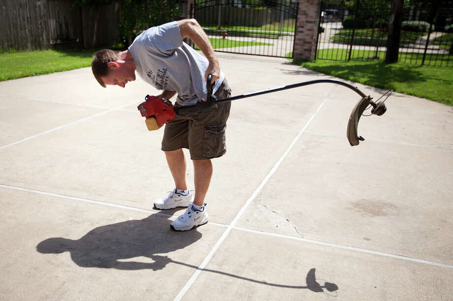 July 30, 2011 | Chris Ferguson gets back to reality tries to repair the family's lawn trimmer, which was broken while he was on orbit, after returning home from the final shuttle mission. Photo: Smiley N. Pool, Houston Chronicle / © 2011  Houston Chronicle