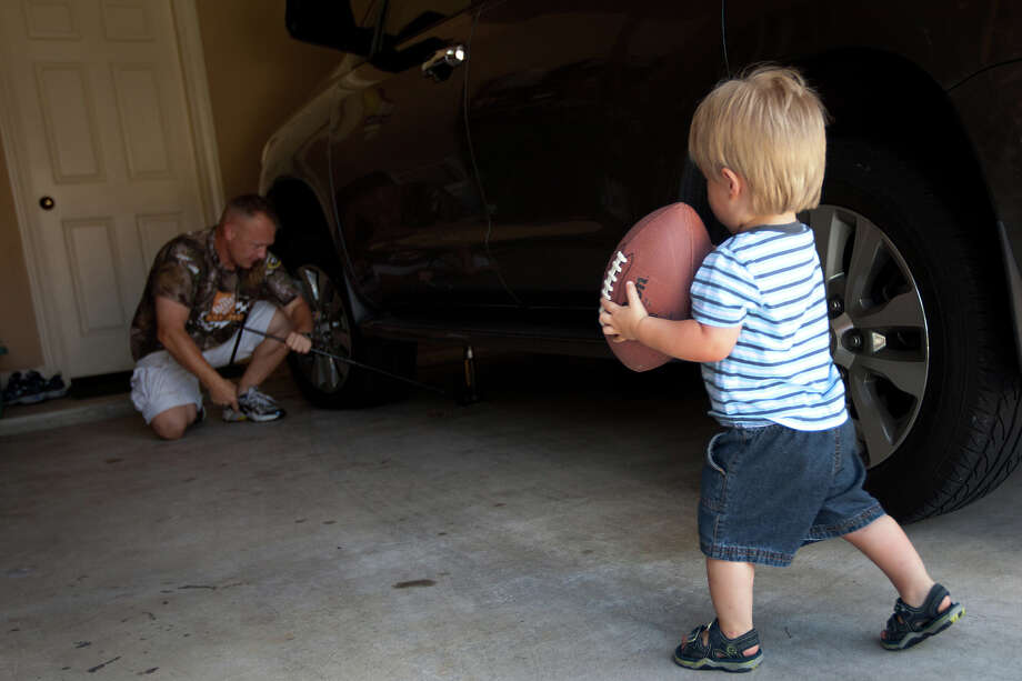 July 30, 2011   Doug Hurley fixes a flat tire in his garage as his son Jack watches as life returns to normal after the final shuttle mission. Photo: Smiley N. Pool, Houston Chronicle / © 2011  Houston Chronicle
