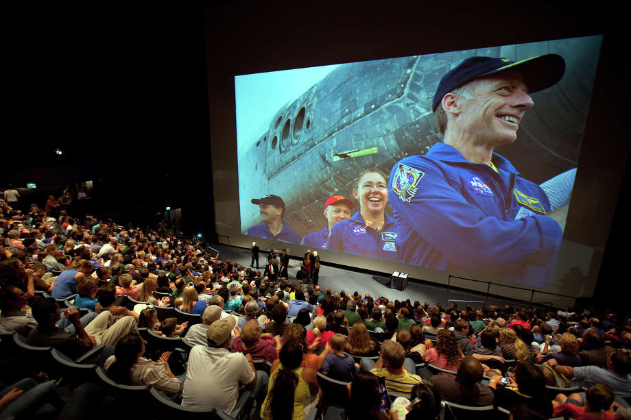 Aug. 3, 2011 | A crowded auditorium of visitors watches a slideshow of the STS-135 crew during a public debrief featuring the crew at Space Center Houston. Photo: Smiley N. Pool, Houston Chronicle / © 2011  Houston Chronicle
