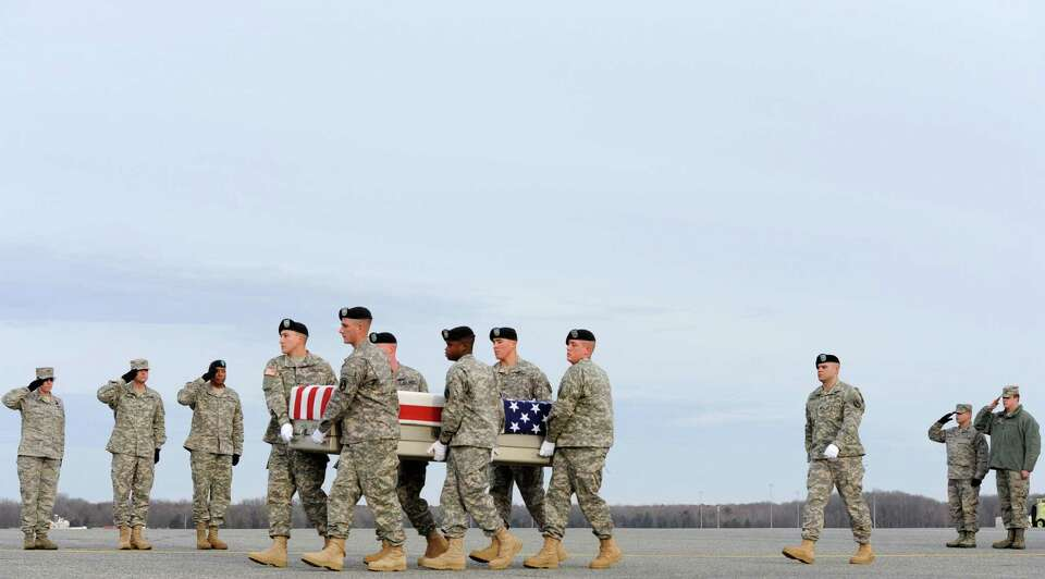 An Army carry team moves a transfer case containing the remains of Pfc. Markie T. Sims, Monday at Do