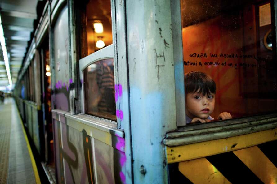 A child looks through the window of a wooden carriage car on the historic subway system, Line A, in