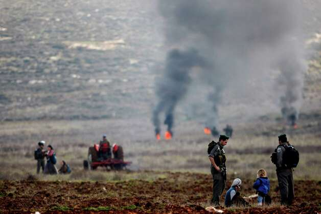 Surrounded by Israeli border police Jewish settlers from the Esh Kodesh settlement outpost sit in a field in an attempt to prevent Palestinians from farming land in the northern West Bank, on Wednesday. Both the settlers and Palestinians living in the area claim ownership of the disputed land. Photo: AP