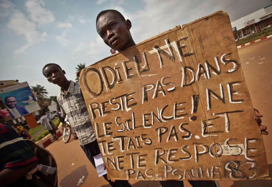 "A protester holds a placard in French reading ""O God, do not remain silent! Do not hold your peace or be still. Psalm 83"" as members of the city's churches hold a demonstration calling for peace as negotiators prepare for talks with rebels from the north, in downtown Bangui, Central African Republic on Saturday. The U.N. Security Council urged rebels in the Central African Republic on Friday to halt their military offensive, withdraw from cities they have seized, and take part in negotiations to find a political solution to the impoverished country's longstanding problems. Photo: AP"