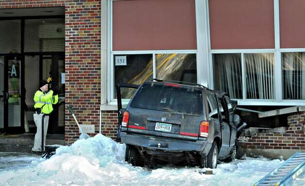 A Minnesota State Patrol investigator photographs the scene of an accident where a vehicle struck the side of St. Katharine Drexel School in St. Cloud, Minn., on Friday. The driver was transported to St. Cloud Hospital. No one else was injured. (AP Photo/The St. Cloud Times, Dave Schwarz) Photo: AP