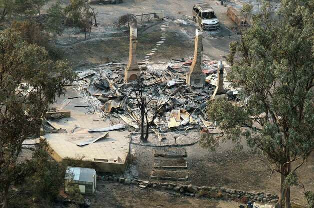 A charred vehicle sits near the remains of a destroyed home following a wildfire near Dunalley, east of the Tasmanian capital of Hobart, Australia, on Saturday.  Australian officials battled a series of wildfires amid scorching temperatures across the country on Saturday, with one blaze destroying dozens of homes in the island state of Tasmania. Photo: AP