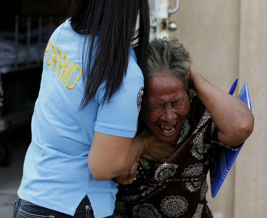 Aniolina Caimol, 63, the grandmother of shooting victim Micaela Caimol, 7, cries after viewing her grand daughter inside a morgue of a private hospital in Kawit township, Cavite province 10 miles south of Manila, Philippines on Friday. A man who was apparently intoxicated has fatally shot eight people, including a child who tried to shield herself behind seat cushions, before he was gunned down by police in a town near the Philippine capital, officials said Friday. Photo: AP