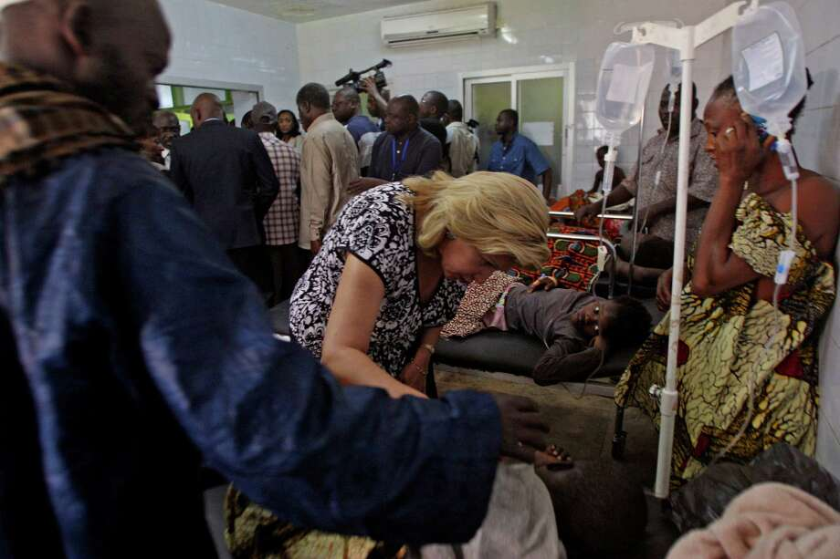 Ivory Coast First Lady Dominique Ouattara, center left, speaks with a person injured in a stampede as they are treated at a hospital in Abidjan, Ivory Coast, on Tuesday. At least 61 people were killed early Tuesday in a stampede following a New Year's fireworks display in Abidjan, Ivory Coast's commercial center, said officials. The death toll is expected to rise, according to rescue workers. Photo: AP