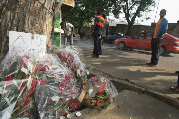 "Flowers are left  by a sign reading ""to our victims"" in Abidjan, Ivory Coast, on Wednesday. Survivors of a stampede in Ivory Coast that killed 61 people, most of them children and teenagers, after a New Year's Eve fireworks display at a stadium said Wednesday that barricades stopped them from moving along a main boulevard, causing the crush of people. Ivory Coast President Alassane Ouattara ordered three days of national mourning and launched an investigation into to the causes of the tragedy but two survivors, in interviews with The Associated Press, indicated why so many died in what would normally be an open area, the Boulevard de la Republic. An estimated 50,000 people had gathered in Abidjan's Plateau district to watch the fireworks. Photo: AP"