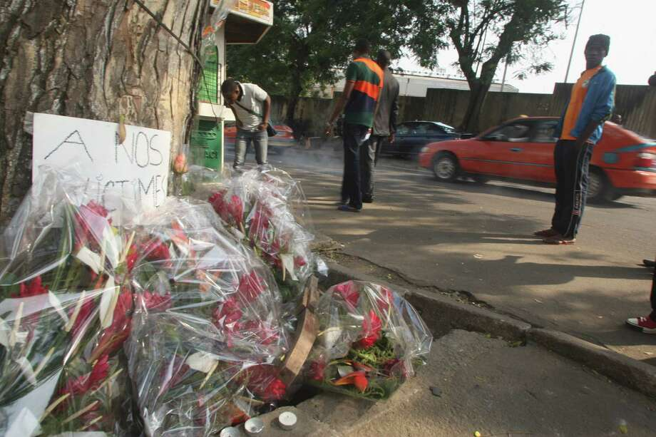 """Flowers are left  by a sign reading """"to our victims"""" in Abidjan, Ivory Coast, on Wednesday. Survivors of a stampede in Ivory Coast that killed 61 people, most of them children and teenagers, after a New Year's Eve fireworks display at a stadium said Wednesday that barricades stopped them from moving along a main boulevard, causing the crush of people. Ivory Coast President Alassane Ouattara ordered three days of national mourning and launched an investigation into to the causes of the tragedy but two survivors, in interviews with The Associated Press, indicated why so many died in what would normally be an open area, the Boulevard de la Republic. An estimated 50,000 people had gathered in Abidjan's Plateau district to watch the fireworks. Photo: AP"""
