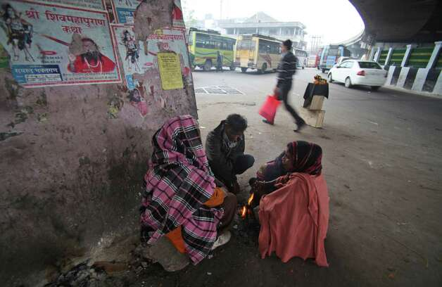 Homeless Indians warm themselves near a fire on a cold and foggy morning in Jammu, India, on Saturday. More than 100 people have died of exposure as northern India deals with historically cold temperatures. Photo: AP