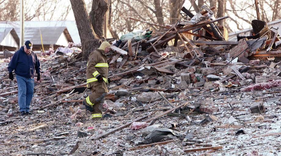 Tony Ventimiglia, left, an investigator with the Illinois State Fire Marshal's Office and John Gusewelle,  chief of the Prairietown Fire Department, walk through the scattered remains of a one-and-a-half story frame house in Worden, Ill., on Thursday. A suspected propane gas leak early Thursday blew the vacant home into splinters in a blast that could be heard at least 15 miles away. There were no injuries reported.  (AP Photo/The Telegraph,John Badman)  Photo: AP