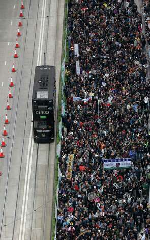 Thousands of anti-government protesters march to the government headquarters on New Year's Day in Hong Kong on Tuesday as they call for the resignation of Hong Kong Chief Executive Leung Chun-ying. Photo: AP