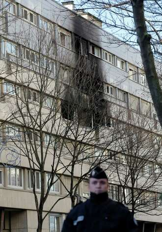 A policeman stands next to a building where a fire in an apartment killed five people, including two children and injured around 18, in Gennevilliers, outside Paris,  on Wednesday. Gennevilliers is among the poorest suburbs of Paris, and many of its residents live in large public housing blocks. Investigators have not yet determined a cause for the overnight fire. Photo: AP
