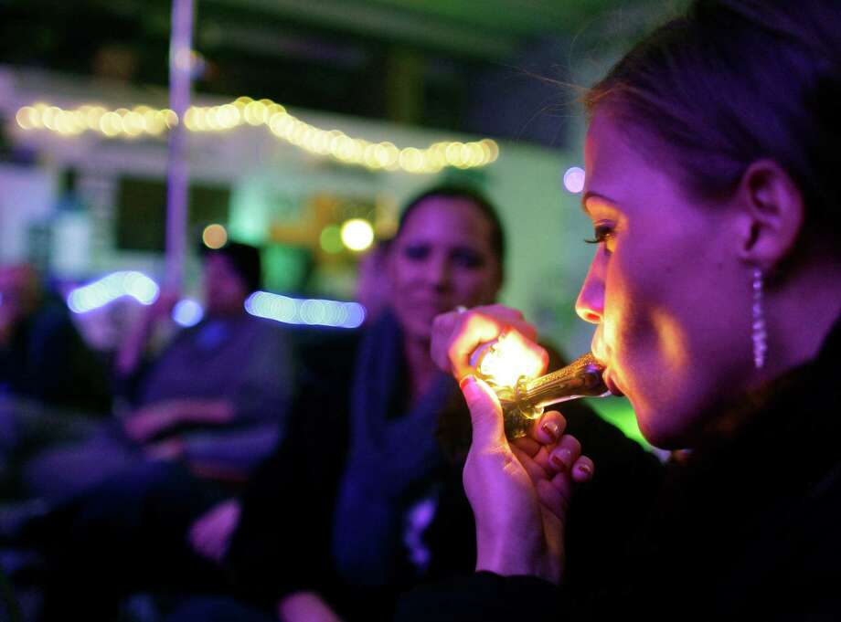 Rachel Schaefer of Denver smokes marijuana on the official opening night of Club 64, a marijuana-specific social club, where a New Year's Eve party was held, in Denver, on Monday. The club shut down the next day. On Election Day, Nov. 6, 2012, a plurality of Coloradans voted in favor of Proposition 64 to legalize recreational marijuana. Photo: AP