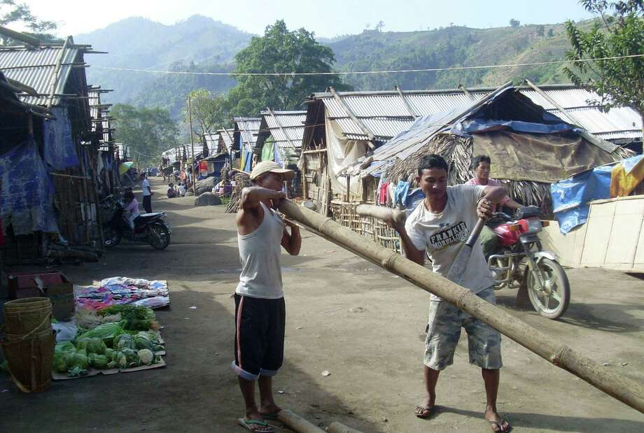 Kachin men cut bamboo to build huts at the Hpun Lum Yang IDP camp near Laiza where Kachin Independence Army is headquartered, northern Myanmar, on Friday. The KIA said Thursday that military air attacks against them were continuing, but that the guerrillas still held key positions protecting their main base. Photo: AP