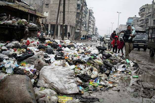 A family crosses a street piled with rubbish in Aleppo, Syria, on Saturday. The revolt against President Bashar Assad started in March 2011 began with peaceful protests but morphed into a civil war that has killed more than 60,000 people, according to a recent United Nations recent estimate. Photo: AP