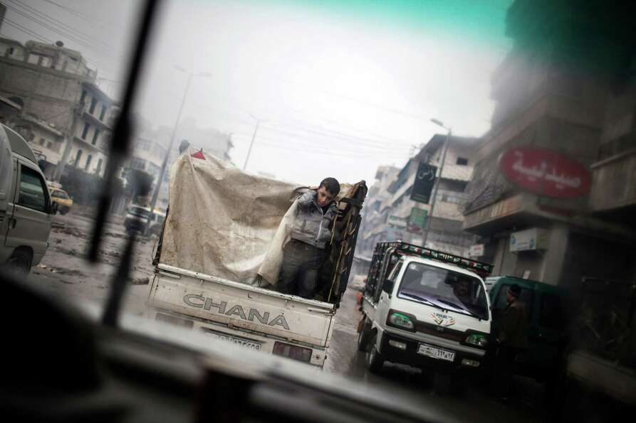 A boy is seen through a car window as he rides on the back of a truck in the streets of Aleppo, Syri