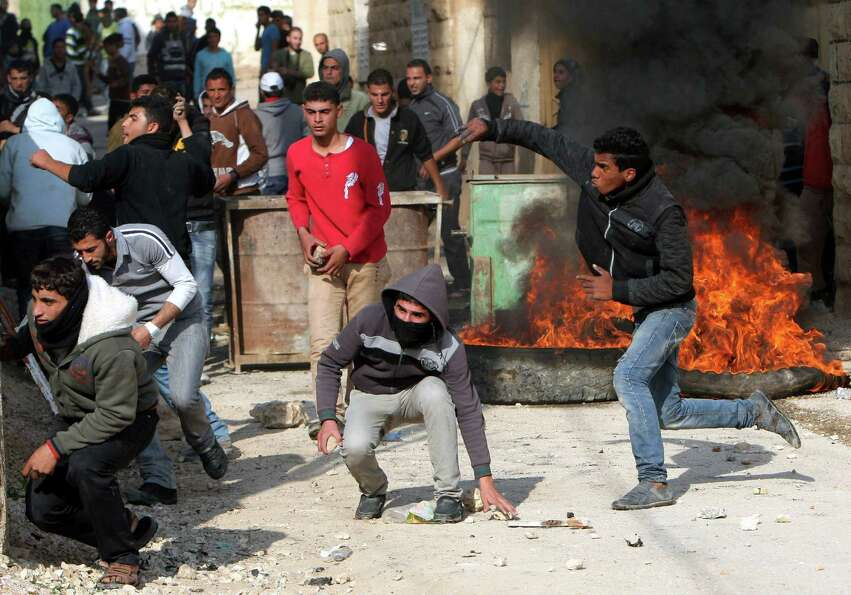 Palestinians hurl stones at Israeli soldiers, not seen, during clashes in the West Bank village of T
