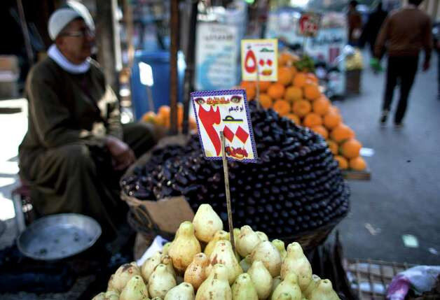 "An Egyptian street vendor displays fruits with price tags in Arabic that reads ""5 and 3 Egyptian pounds,"" in Cairo, Egypt, on Wednesday. The Egyptian pound slipped further against the dollar on Monday, a downward plunge on the first two days of trading under a new system, as the president tried to assure a worried public that the crisis atmosphere will end soon. Photo: AP"
