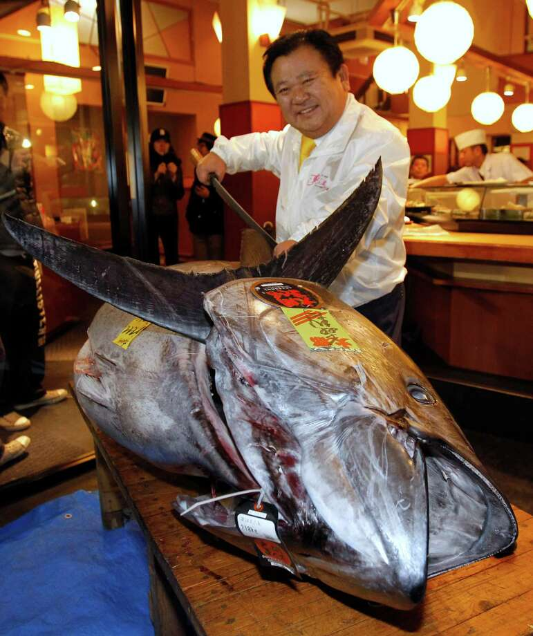 Kiyoshi Kimura, president of Kiyomura Co., poses with a bluefin tuna in front of his Sushi Zanmai restaurant near Tsukiji fish market in Tokyo on Saturday. The bluefin tuna caught off northeastern Japan fetched a record 155.40 million yen, or about $1,763,000, in the first auction of the year at the fish market. The tuna was caught off Oma in Aomori prefecture. Photo: AP
