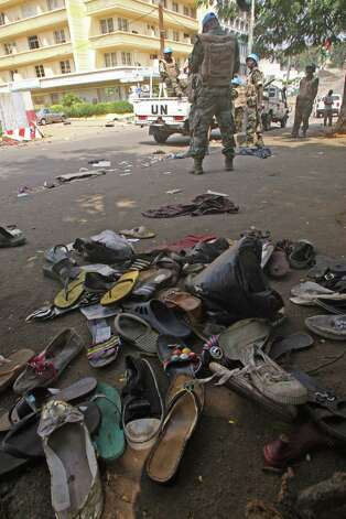 U.N. troops stand near the shoes  of people that were involved in a stampede in Abidjan, Ivory Coast on Tuesday. At least 61 people were killed early Tuesday in a stampede following a New Year's fireworks display in Abidjan, Ivory Coast's commercial center, said officials. The death toll is expected to rise, according to rescue workers. The majority of those killed were young people between eight and 15 years old who were trampled after the fireworks festivities in Abidjan's Plateau district, at about 1 a.m. Tuesday, said Col. Issa Sako, of the fire department rescue team. Photo: AP