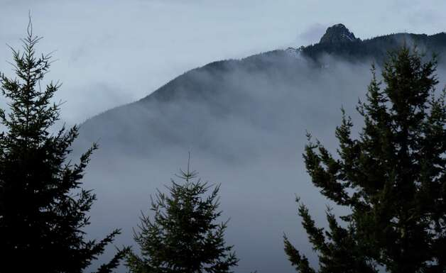 Rugged terrain surrounds the summit of Mount Si, upper right on Friday near North Bend, Wash. Searchers in the air and on the ground were looking for 29-year-old Kurt Ruppert of Lake City, Fla., who has been missing since a skydiving trip on Thursday. Photo: AP