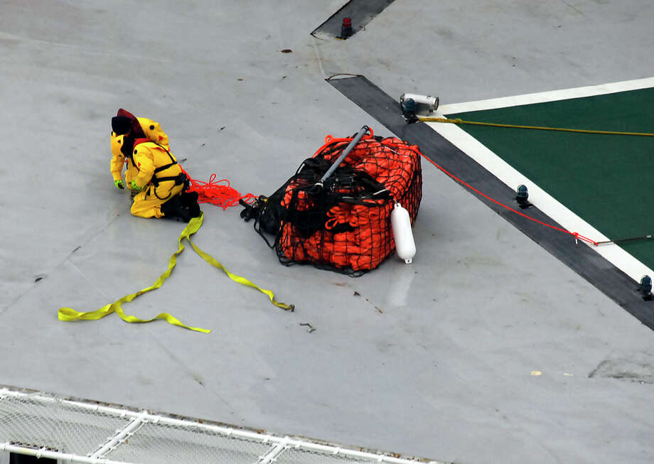 A photo provided by the U.S. Coast Guard shows a salvage team wrapping up lines from an emergency towing system delivered to the deck of the petroleum drilling ship Kulluk  on Wednesday in the Gulf of Alaska. The grounding of the drill ship on a remote Alaska island has refueled the debate over oil exploration in the U.S. Arctic Ocean. Photo: AP