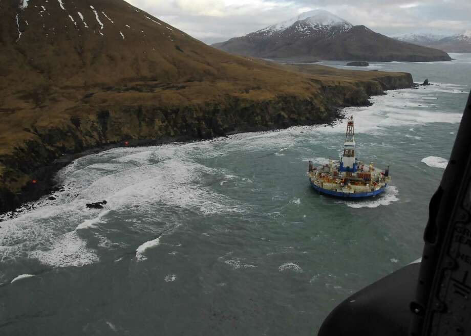 In this image provided by the U.S. Coast Guard shows two life rafts sit on the beach adjacent as the conical drilling unit Kulluk sits grounded 40 miles southwest of Kodiak City on Thursday. The Kulluk grounded after many efforts by tug vessel crews and Coast Guard crews to move the vessel to safe harbor during a winter storm.Calls for federal scrutiny of Royal Dutch Shell PLC drilling operations in Arctic waters swelled Thursday with a request for a formal investigation by members of Congress. Photo: AP